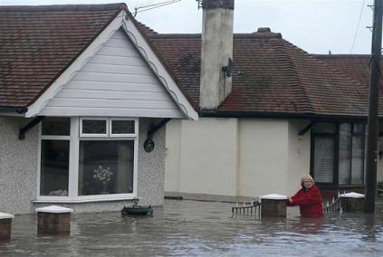 A woman walks through flood water in a street in Rhyl, north Wales
